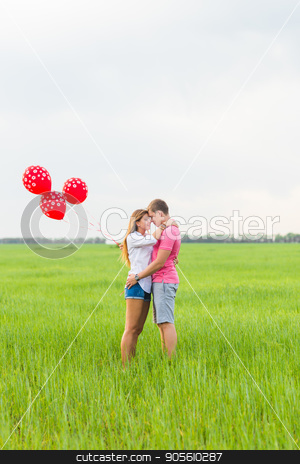 beautiful young couple hugging and kissing in a field with colored balloons stock photo, beautiful young couple hugging and kissing in a field with colored balloons by Satura86