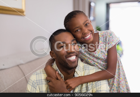 Portrait of happy father and daughter in living room stock photo, Portrait of happy father and daughter in living room at home by Wavebreak Media