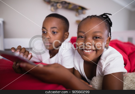 Cheerful girl with brother using mobile phone on bed at home stock photo, Portrait of cheerful girl with brother using mobile phone on bed at home by Wavebreak Media
