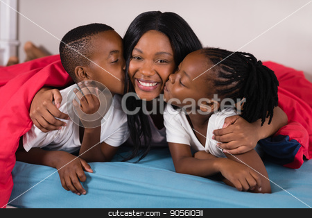 Siblings kissing their mother while lying on bed stock photo, Siblings kissing their mother while lying on bed at home by Wavebreak Media