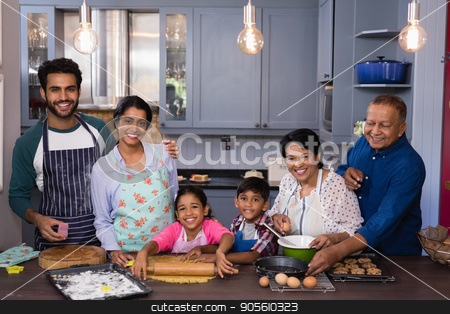 Portrait of multi-generation family smiling together while preparing food stock photo, Portrait of multi-generation family smiling together while preparing food in kitchen at home by Wavebreak Media