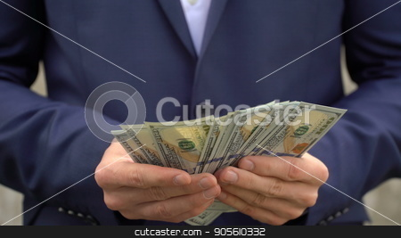 Young businessman shows his money close-up stock photo, Young businessman shows his money close up by petr zaika
