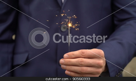 Young businessman in blue suit holds a bengal fire in his hand stock photo, Young businessman in blue suit holds a bengal fire in his hand by petr zaika