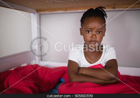Portrait of upset little girl sitting on bed stock photo, Portrait of upset little girl sitting on bed at home by Wavebreak Media