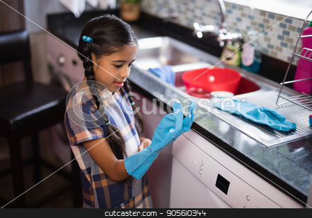 Cute girl wearing glove while standing in kitchen stock photo, Cute girl wearing glove while standing in kitchen at home by Wavebreak Media