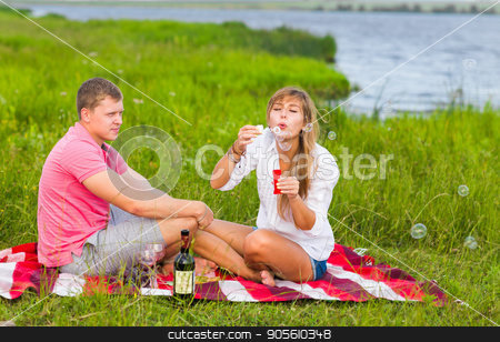 Beautiful couple having a picnic in nature and blowing bubbles stock photo, Beautiful couple having a picnic in nature and blowing bubbles by Satura86
