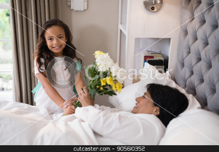 Portrait of girl giving bouquet to sick grandmother at home stock photo, Portrait of smiling girl giving bouquet to sick grandmother at home by Wavebreak Media