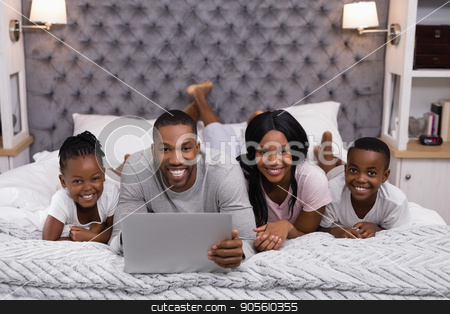 Portrait of smiling family using laptop while lying together on bed stock photo, Portrait of smiling family using laptop while lying together on bed at home by Wavebreak Media