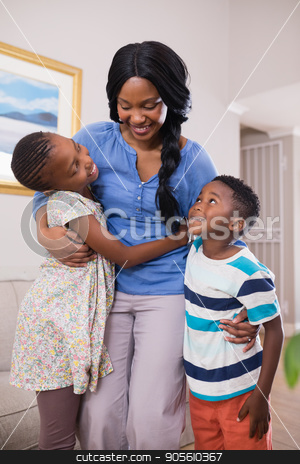 Smiling mother with children in living room stock photo, Smiling mother with children in living room at home by Wavebreak Media