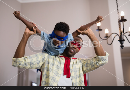 Father and son wearing superhero costume at home stock photo, Playful father and son wearing superhero costume at home by Wavebreak Media