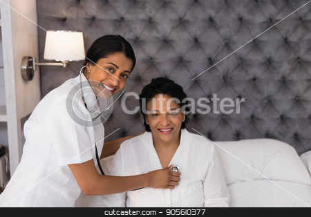 Smiling nurse examining mature woman resting on bed at home stock photo, Portrait of smiling nurse examining mature woman resting on bed at home by Wavebreak Media