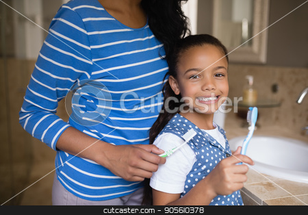 Smiling girl with mother brushing teeth in bathroom stock photo, Portrait of smiling girl with mother brushing teeth in bathroom by Wavebreak Media
