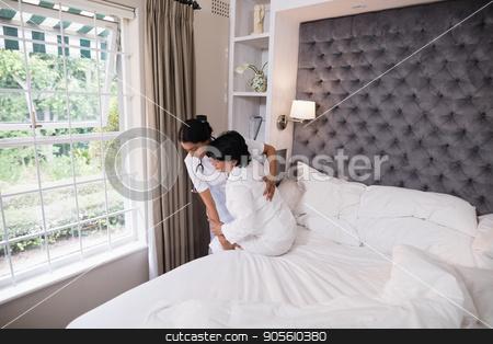 Nurse helping patient on bed at home stock photo, Nurse helping female patient on bed at home by Wavebreak Media
