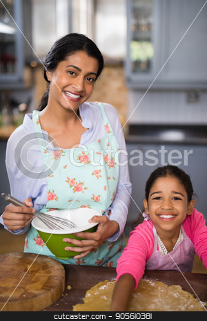 Portrait of smiling girl preparing food with mother at home stock photo, Portrait of smiling girl preparing food with mother in kitchen at home by Wavebreak Media