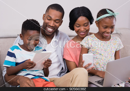 Family using technologies while sitting on sofa at home stock photo, Happy family using technologies while sitting on sofa at home by Wavebreak Media