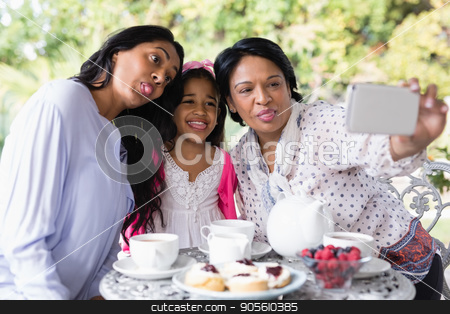 Multi-generation family taking selfie while sitting together by breakfast table stock photo, Multi-generation family taking selfie while sitting together by breakfast table at home by Wavebreak Media