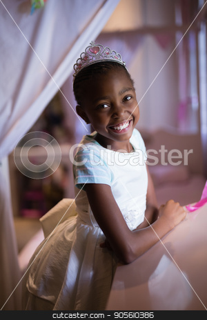 Cheerful girl wearing crown while standing at home stock photo, Portrait of cheerful girl wearing crown while standing at home by Wavebreak Media