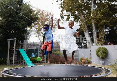 Playful siblings in costumes enjoying on trampoline stock photo, Playful siblings in costumes enjoying on trampoline at lawn by Wavebreak Media