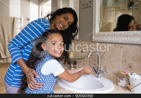 Smiling girl with mother washing hands at bathroom sink stock photo, Portrait of smiling girl with mother washing hands at bathroom sink by Wavebreak Media