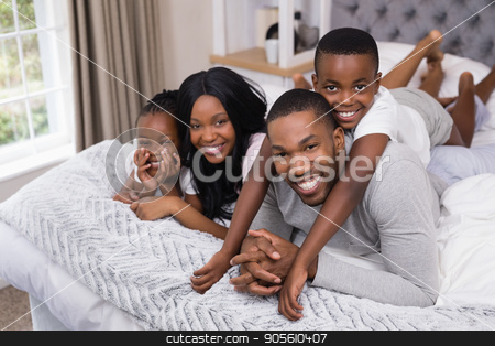 Portrait of happy family lying together in bedroom stock photo, Portrait of happy family lying together in bedroom at home by Wavebreak Media