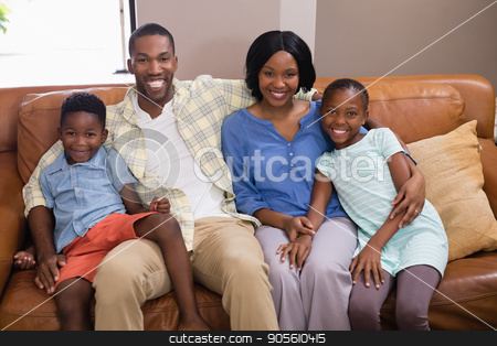 Portrait of happy family sitting on sofa stock photo, Portrait of happy family sitting on sofa at home by Wavebreak Media