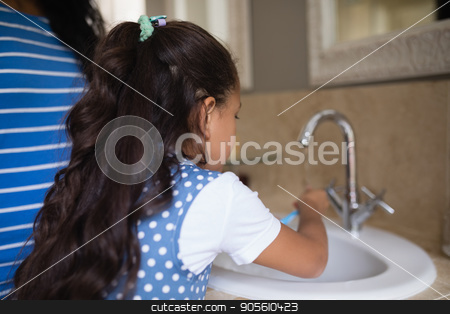 Girl with mother brushing teeth at bathroom sink stock photo, Rear view of girl with mother brushing teeth at bathroom sink by Wavebreak Media