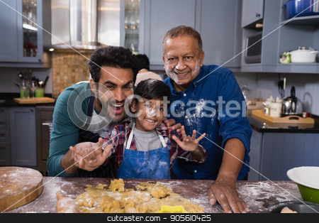 Portrait of multi-generation family standing by dough in kitchen stock photo, Portrait of happy multi-generation family standing together by dough in kitchen at home by Wavebreak Media