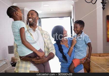 Parents carrying children in living room at home stock photo, Happy parents carrying children in living room at home by Wavebreak Media