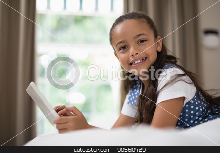 Girl using digital tablet while lying on bed at home stock photo, Portrait of girl using digital tablet while lying on bed at home by Wavebreak Media
