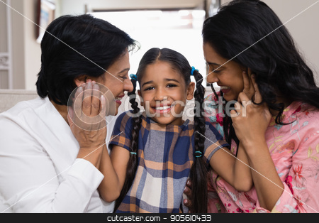 Portrait of cute smiling girl with mother and grandmother stock photo, Portrait of cute smiling girl with mother and grandmother at home by Wavebreak Media
