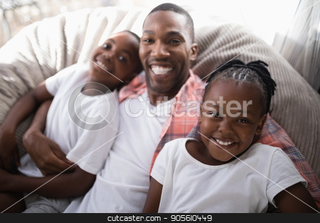 High angle portrait of happy father with daughter and son resting on couch stock photo, High angle portrait of happy father with daughter and son resting on couch at home by Wavebreak Media