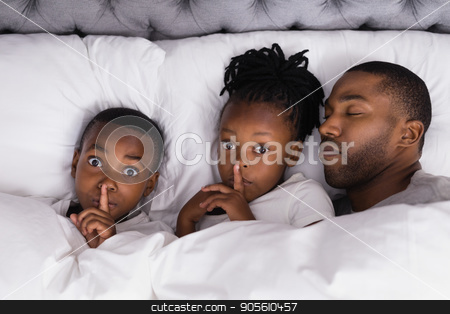 Portrait of siblings with finger on lips by father sleeping in bed stock photo, High angle portrait of siblings with finger on lips by father sleeping in bed at home by Wavebreak Media