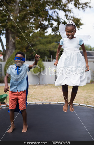 Siblings in costumes jumping on trampoline at lawn stock photo, Full length of siblings in costumes jumping on trampoline at lawn by Wavebreak Media