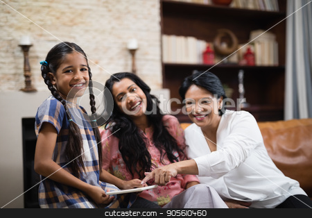 Portrait of happy multi-generation family using digital tablet at home stock photo, Portrait of happy multi-generation family using digital tablet while sitting together on sofa at home by Wavebreak Media