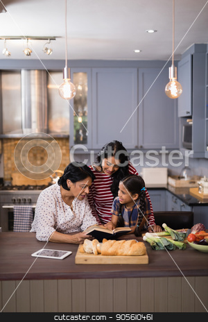 Multi-generation family reading book together in kitchen stock photo, Multi-generation family reading book together in kitchen at home by Wavebreak Media