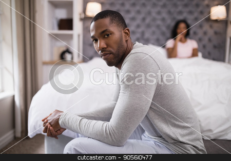 Young man siting while woman resting on bed at home stock photo, Portrait of young man siting while woman resting on bed at home by Wavebreak Media