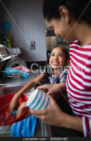 Cute smiling girl helping her mother in kitchen stock photo, Cute smiling girl helping her mother in kitchen at home by Wavebreak Media