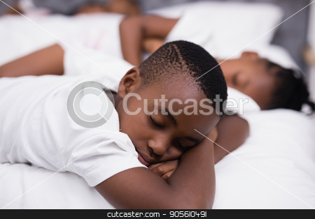 Boy sleeping with sister on bed in background stock photo, Boy sleeping on bed with sister in background at home by Wavebreak Media