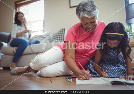 Grandmother and granddaughter coloring book in living stock photo, Grandmother and granddaughter coloring book in living room at home by Wavebreak Media