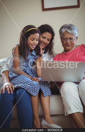 Happy family using laptop in living room stock photo, Happy family using laptop in living room at home by Wavebreak Media