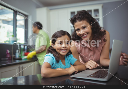 Mother and daughter using laptop in kitchen stock photo, Portrait of mother and daughter using laptop in kitchen at home by Wavebreak Media