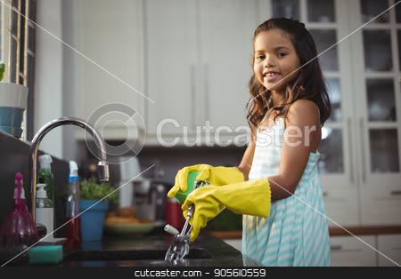 Cute little girl washing utensil in kitchen sink stock photo, Portrait of cute little girl washing utensil in kitchen sink at home by Wavebreak Media