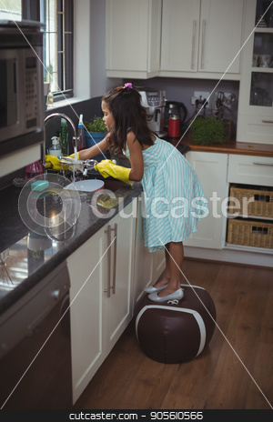Cute little girl washing utensil in kitchen sink stock photo, Cute little girl washing utensil in kitchen sink at home by Wavebreak Media