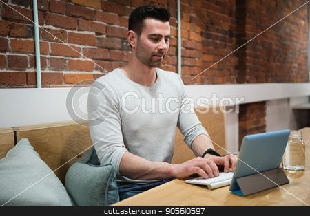 Male executive using digital tablet at desk stock photo, Male executive using digital tablet at desk in office by Wavebreak Media
