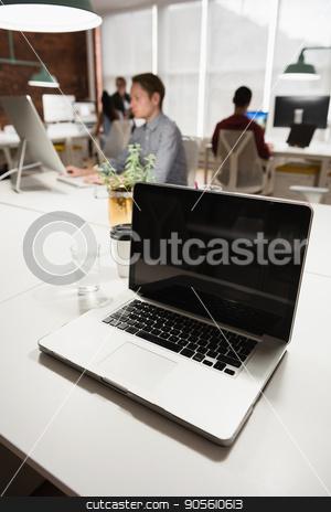 Laptop on table stock photo, Laptop on table in office by Wavebreak Media