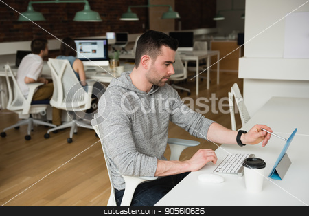 Male executive working on digital tablet stock photo, Male executive working on digital tablet in office by Wavebreak Media
