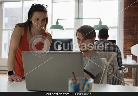 Executives discussing over laptop in office stock photo, Attentive executives discussing over laptop in office by Wavebreak Media