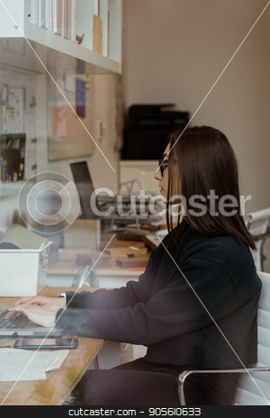 Female executive working on laptop in office stock photo, Attentive female executive working on laptop in office by Wavebreak Media