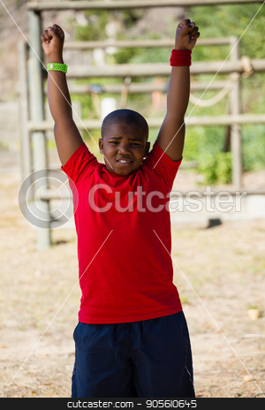 Boy performing stretching exercise during obstacle course training stock photo, Boy performing stretching exercise during obstacle course training in the boot camp by Wavebreak Media