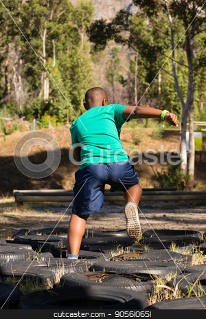 Boy running over tyres during obstacle course training stock photo, Boy running over tyres during obstacle course training in the boot camp by Wavebreak Media